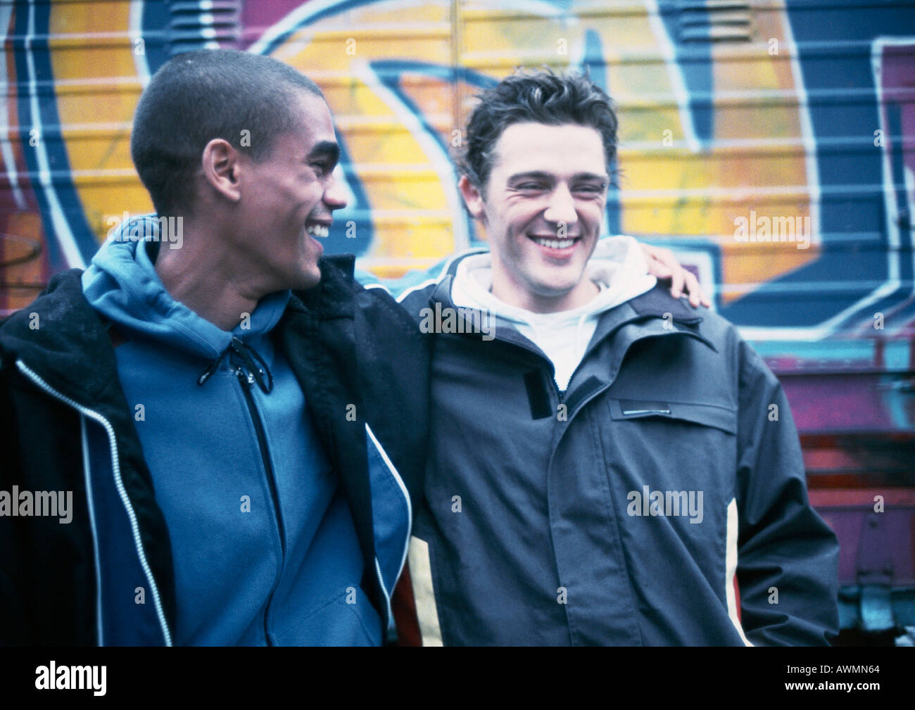 Two young men, one with arm around the other, smiling - Stock Image