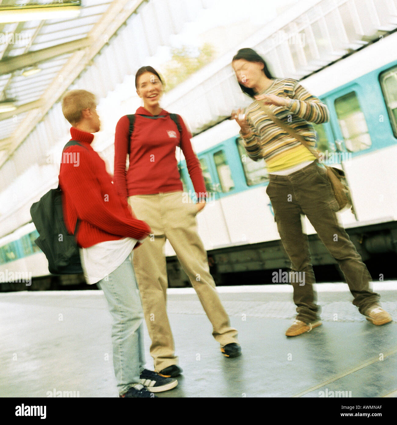 Three teenagers standing on subway platform, blurred - Stock Image
