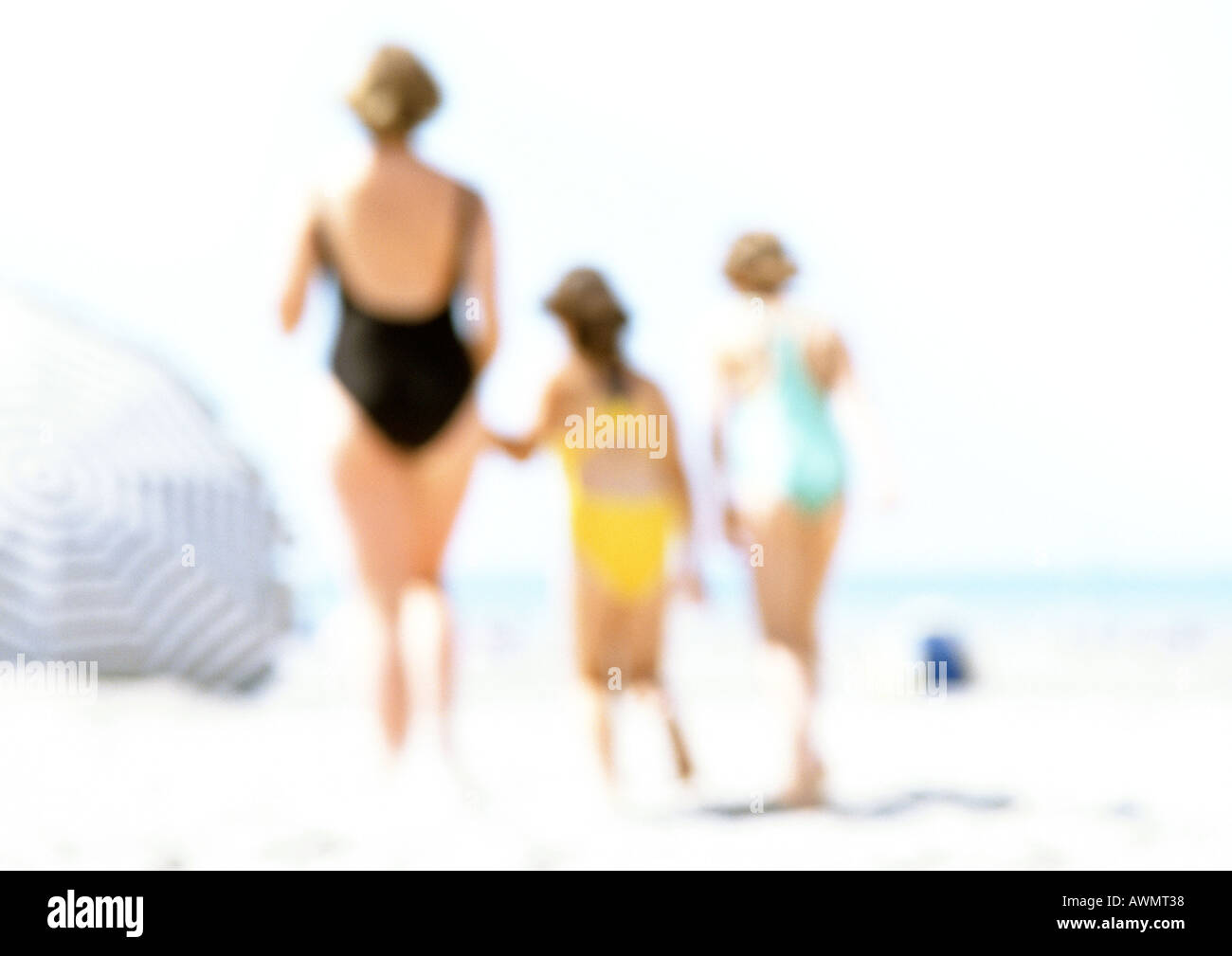 Women and children standing on the beach, blurred - Stock Image