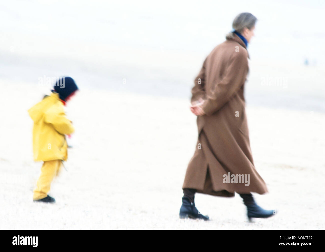 Woman and child in coats walking on beach, blurred - Stock Image