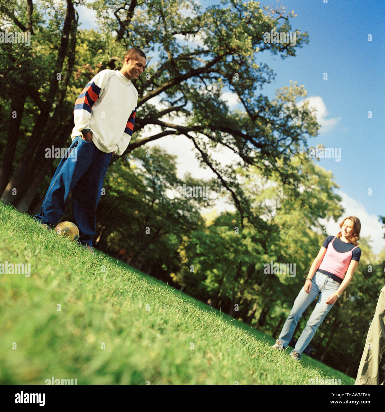 Young man standing on grass with soccer ball, young woman looking at him, low angle view - Stock Image