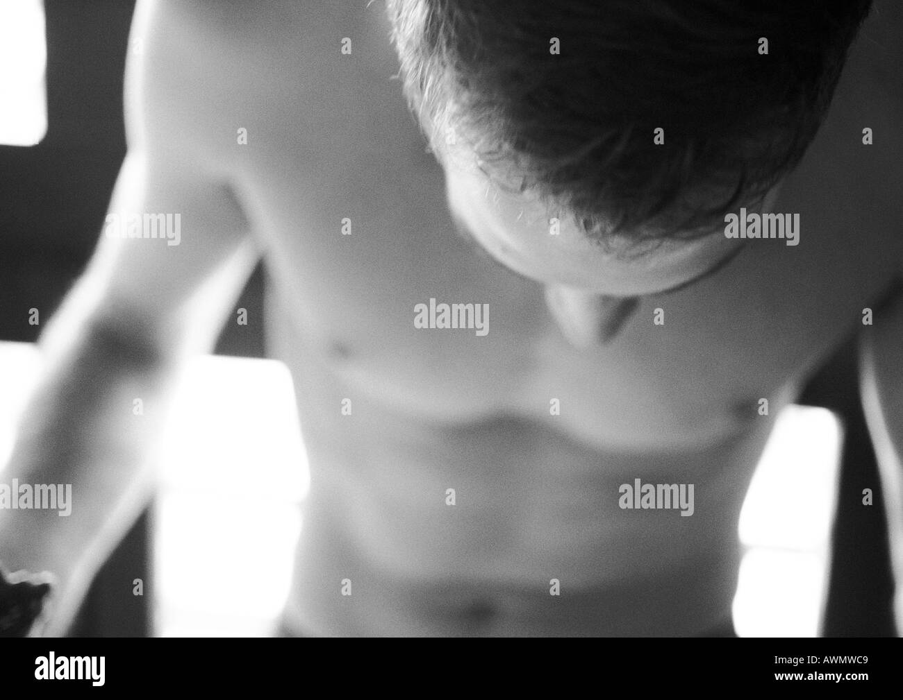 Barechested man looking down,  close-up, black and white. - Stock Image