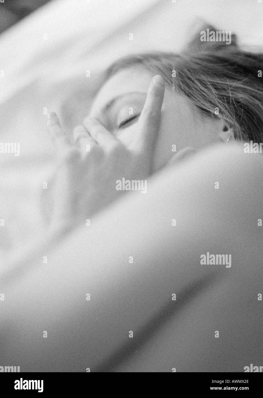 Woman lying on bed, touching face, close-up, black and white - Stock Image