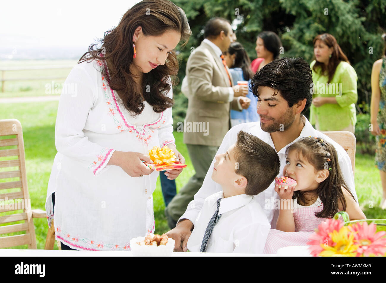 Hispanic mother handing birthday gift to son - Stock Image