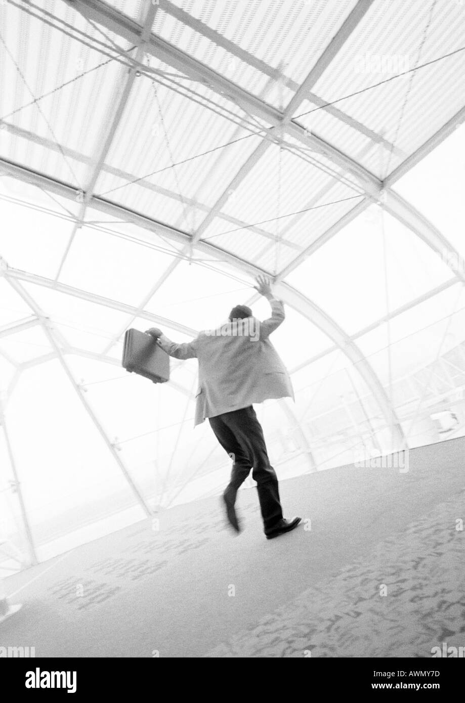 Businessman waving hand and briefcase, rear view, blurred b&w. - Stock Image