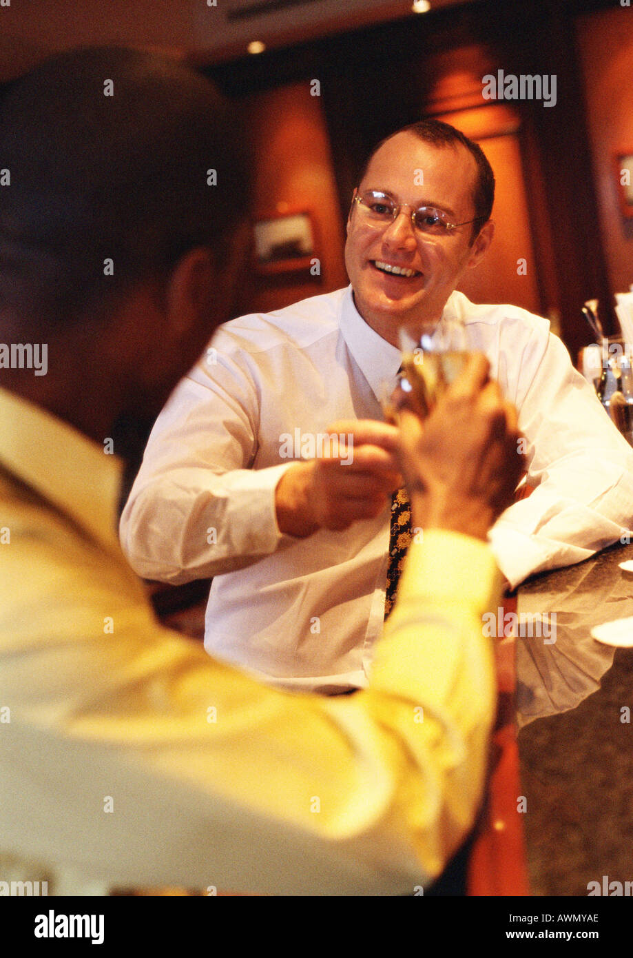 Businessmen raising glasses at bar. - Stock Image