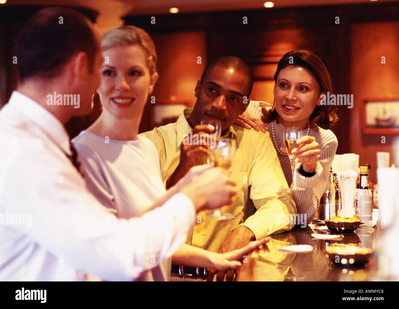 Group of business people raising glasses at bar - Stock Image