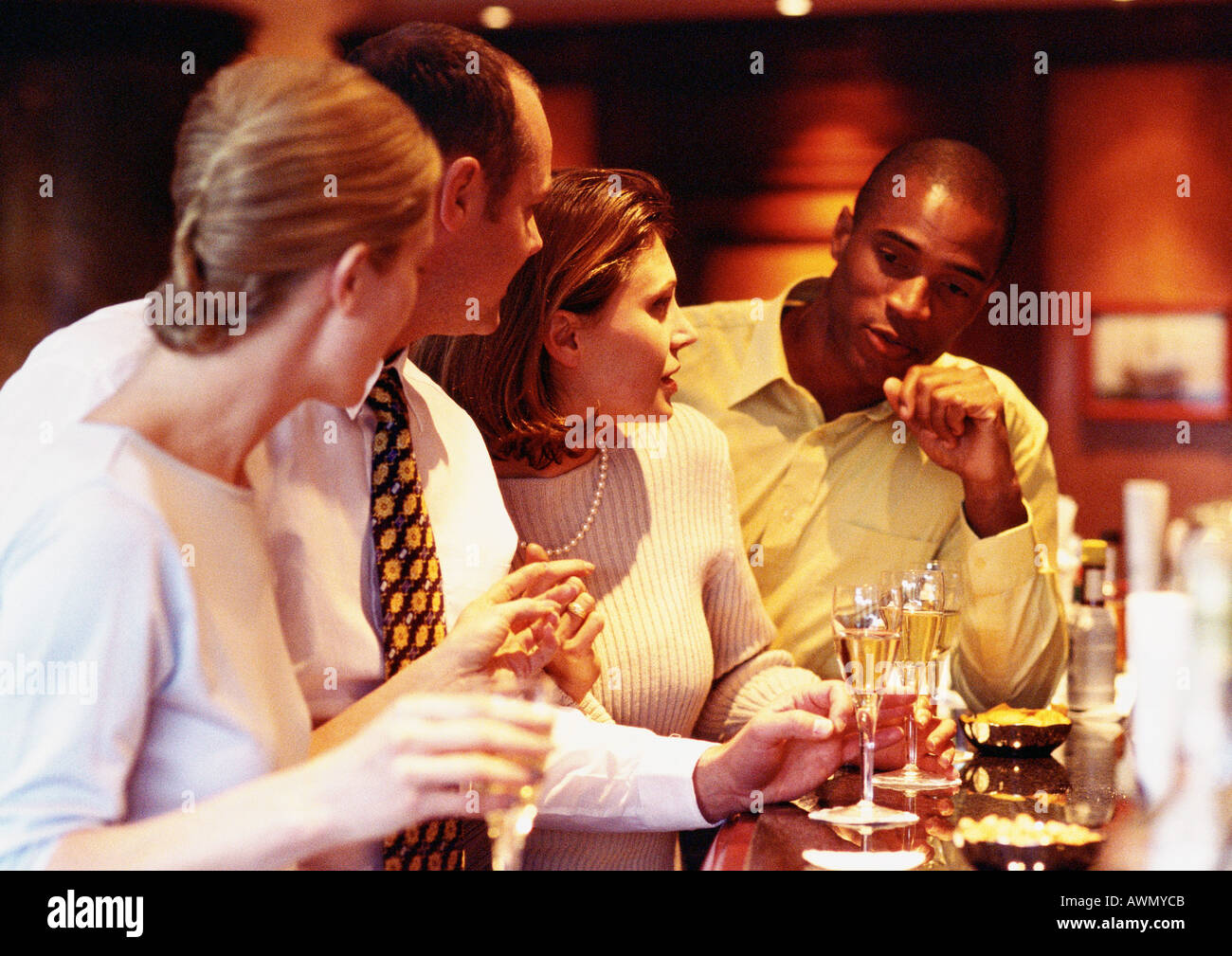 Group of business people socializing at bar. - Stock Image