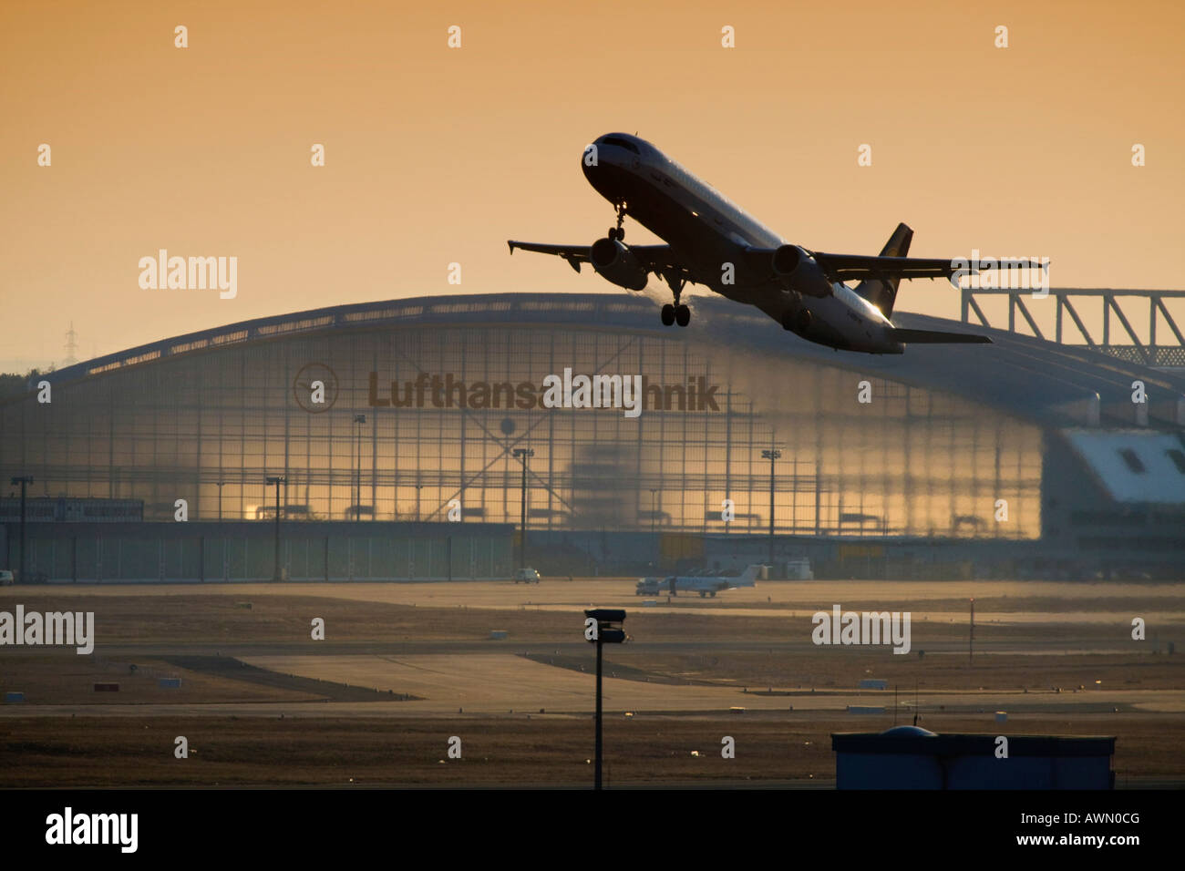 Lufthansa Airbus taking off at dusk, Lufthansa Technik hangar in background, Frankfurt International Airport, Frankfurt, - Stock Image