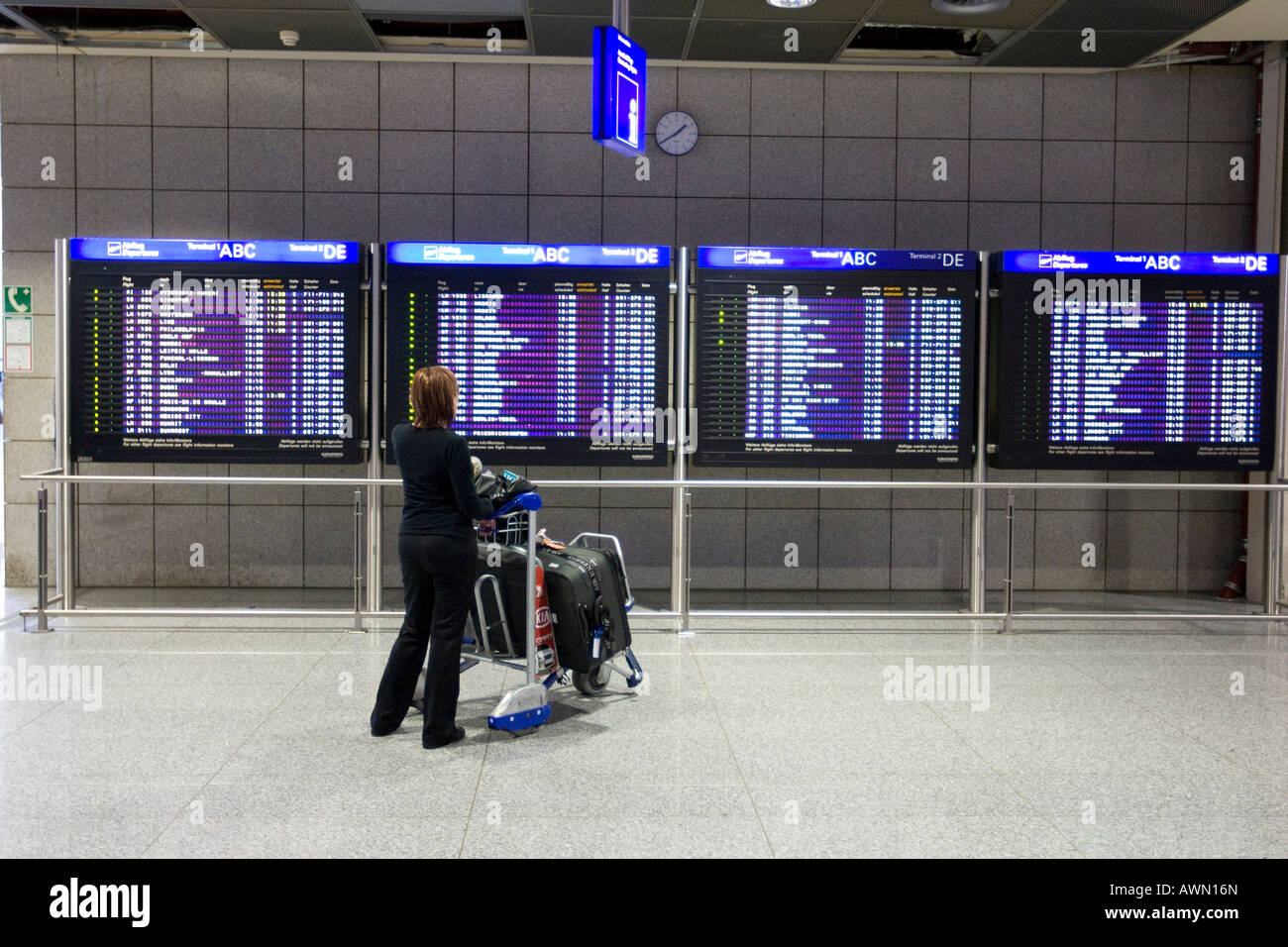 Passenger with luggage cart in front of flight info display screens, Terminal 2, Frankfurt Airport, Frankfurt, Hesse, - Stock Image