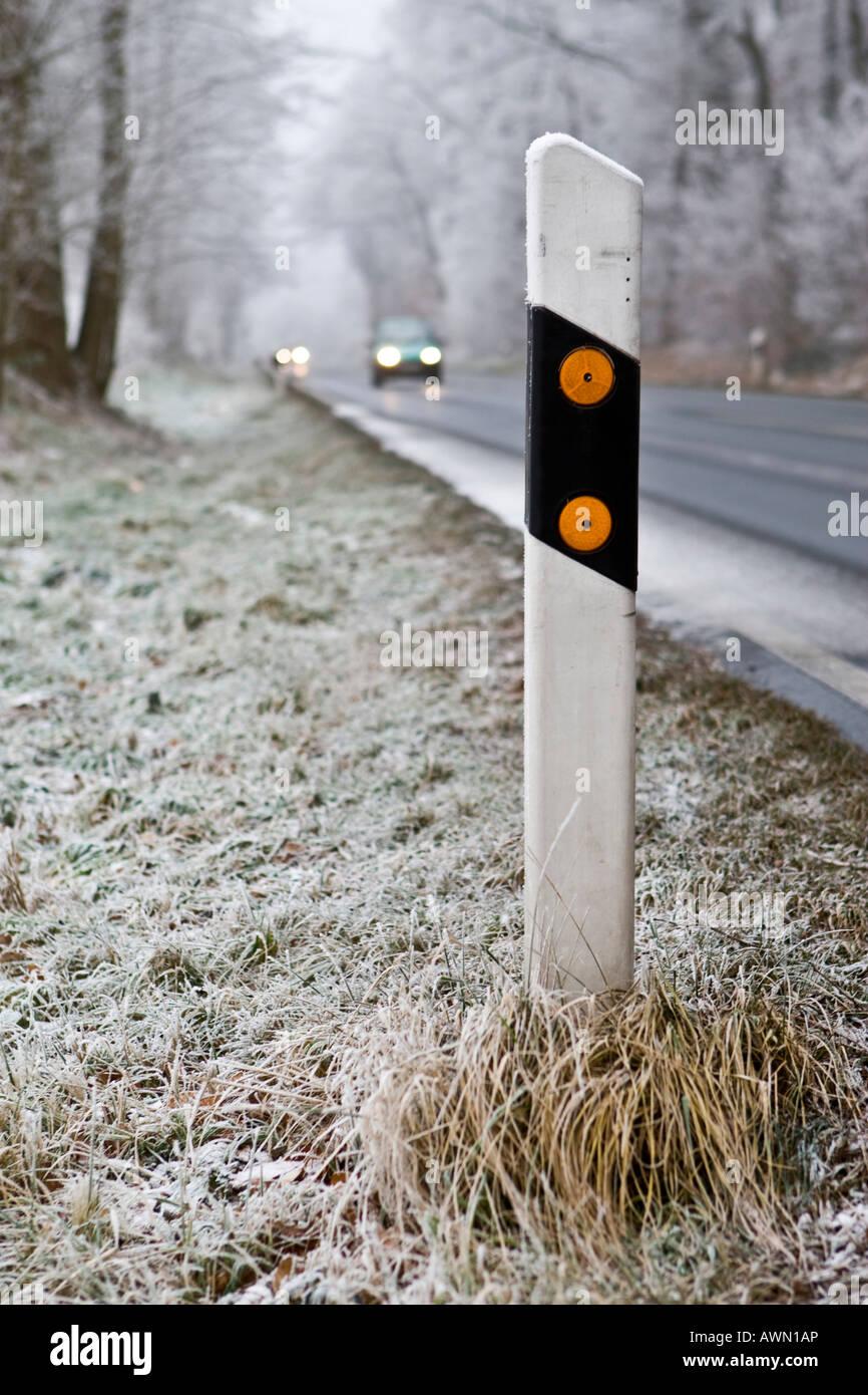 Winter traffic, car driving toward reflector post, Hesse, Germany, Europe - Stock Image