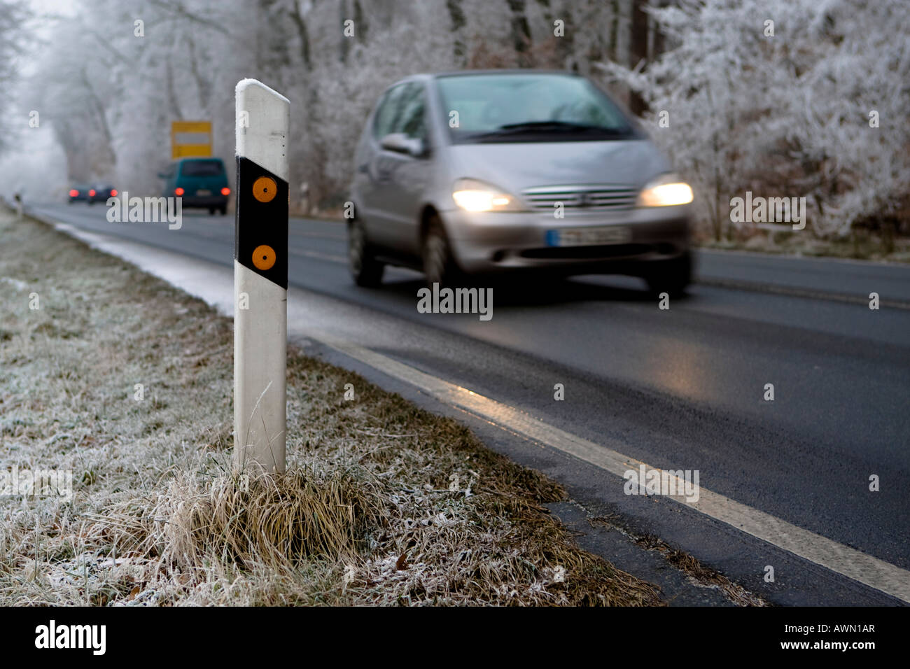 Winter traffic, car driving by reflector post with headlights on, Hesse, Germany, Europe - Stock Image