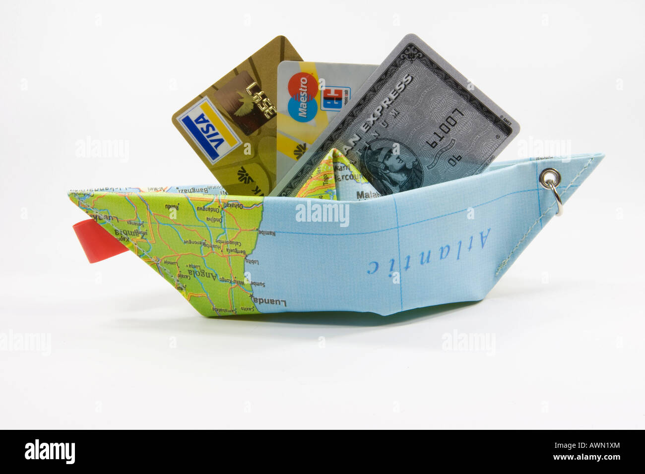 Credit cards and a paper ship made from a map: symbol for payment methods while travelling Stock Photo