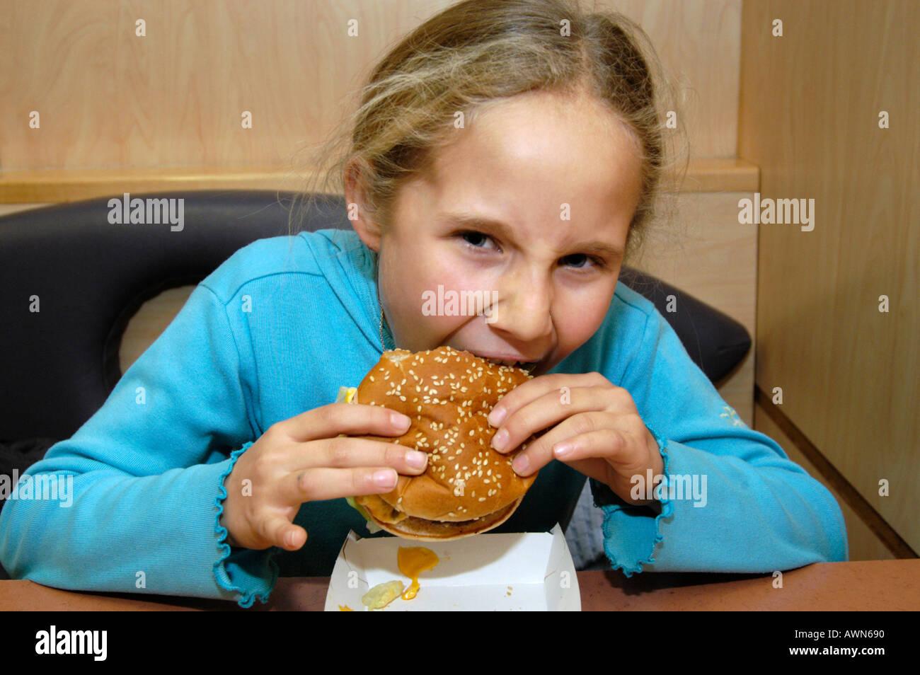Child eating Mcdonald's Burger, UK - Stock Image