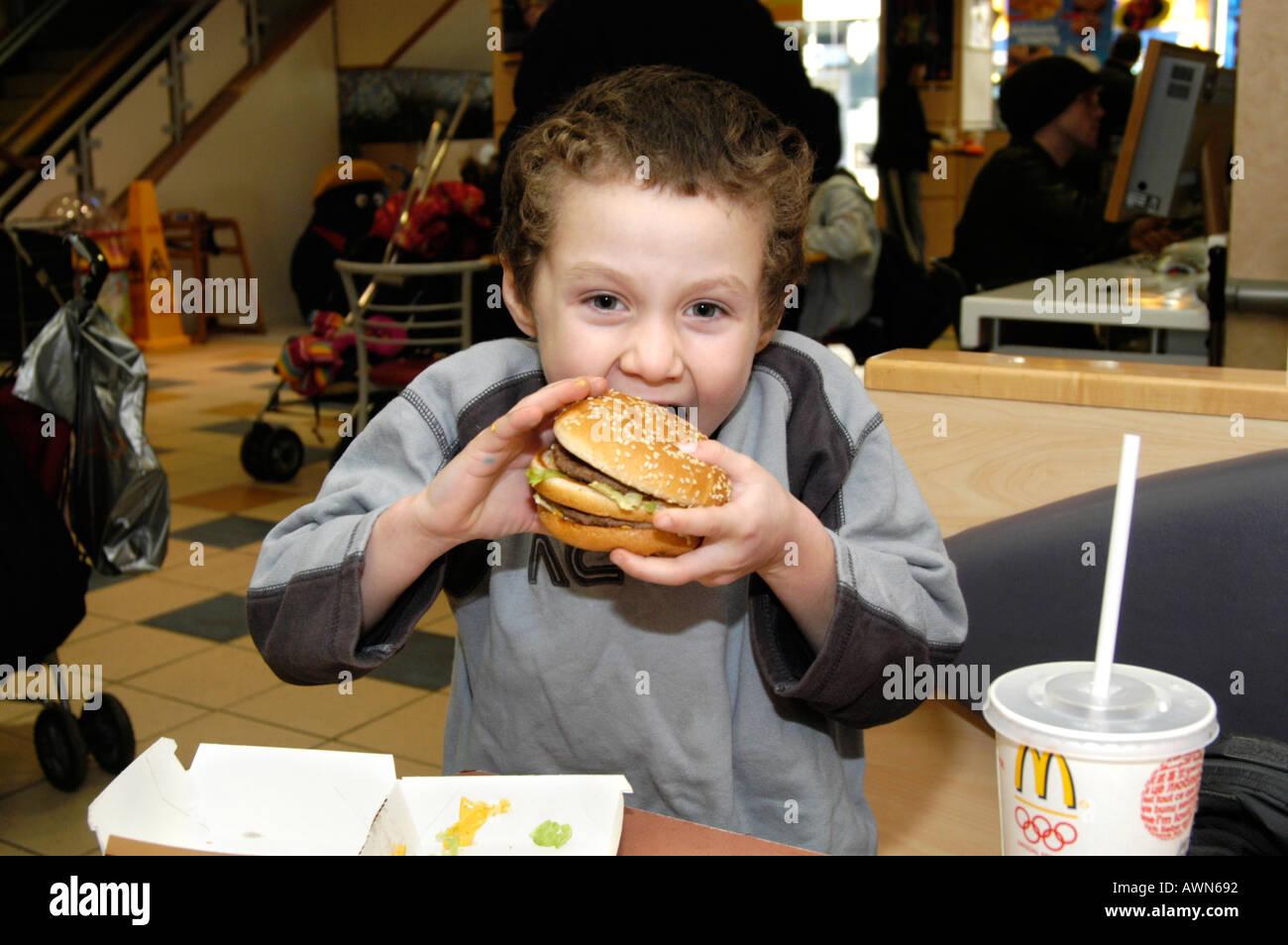 Small boy eating Mcdonald's Big Mac, England UK - Stock Image