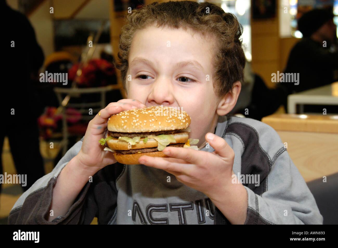 Small boy eating Mcdonald's Big Mac Burger England UK - Stock Image