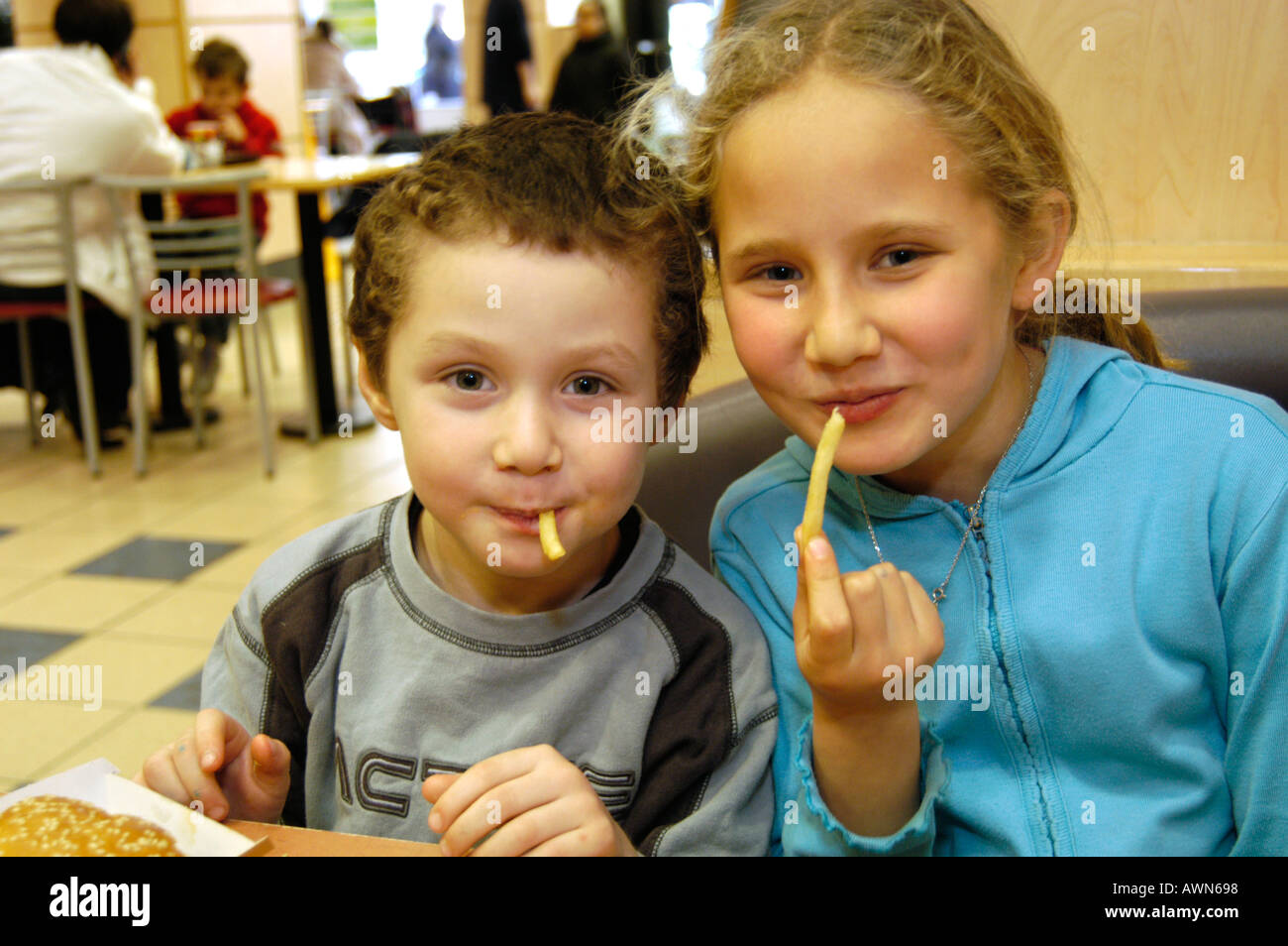 Brother and sister eating Mcdonald's French fries, England, UK - Stock Image