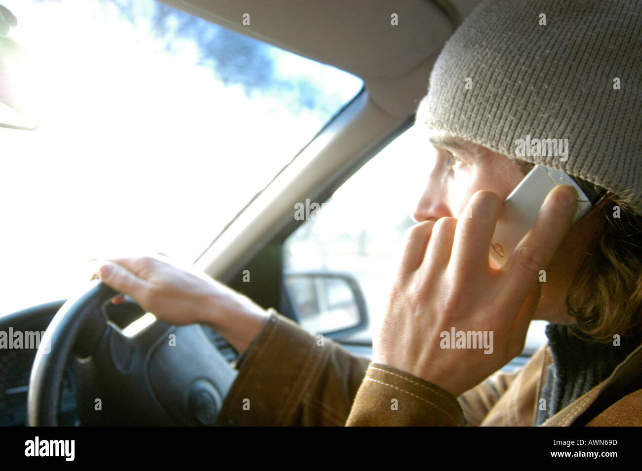 Young man illegally driving car while talking on mobile phone, England, UK - Stock Image