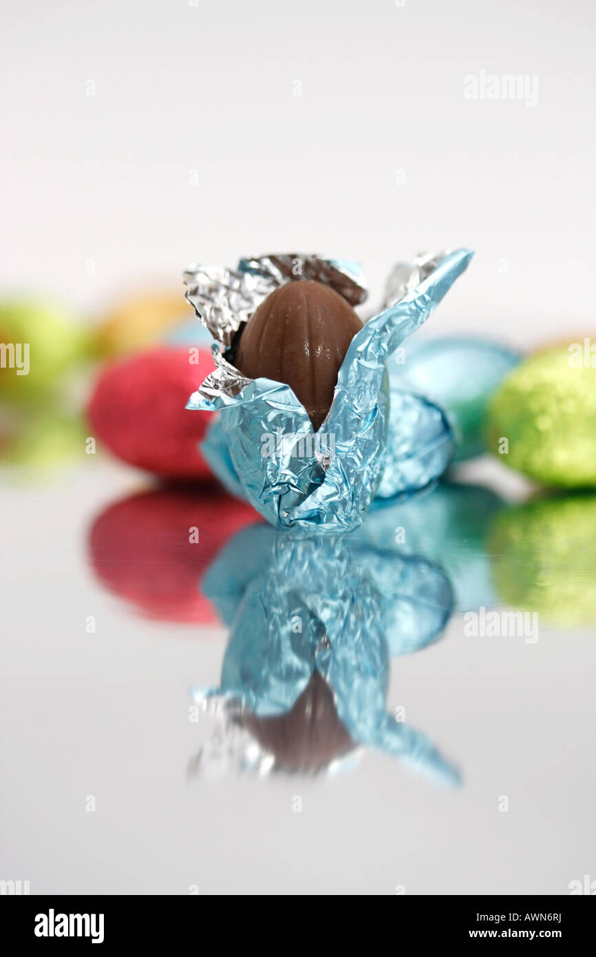 Chocolate Easter eggs laid out on a mirror, one partially unwrapped in the foreground Stock Photo