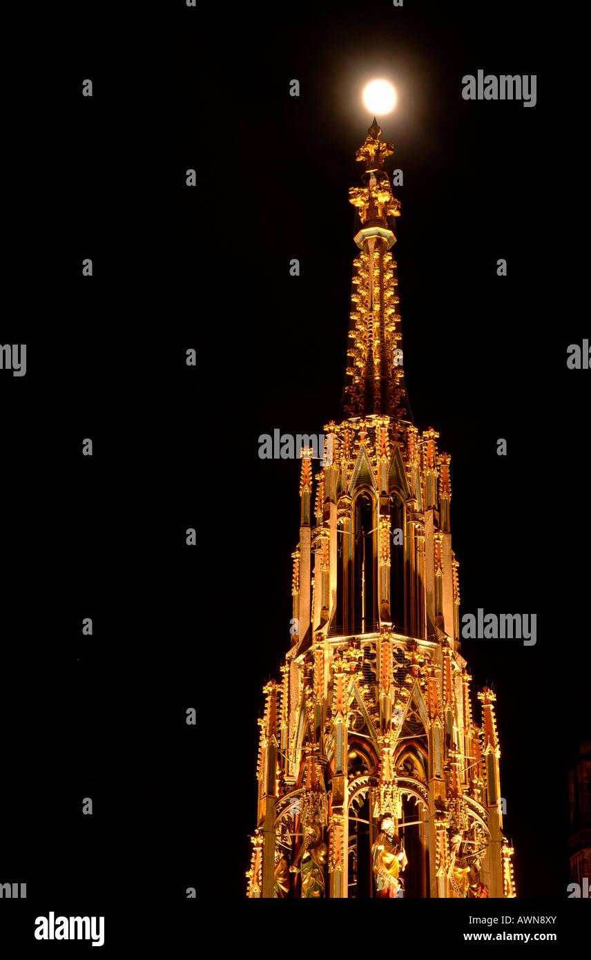 Full moon over the 'Schoene Brunnen' fountain resembling a gothic steeple, Nuremberg, Franconia, Bavaria, - Stock Image