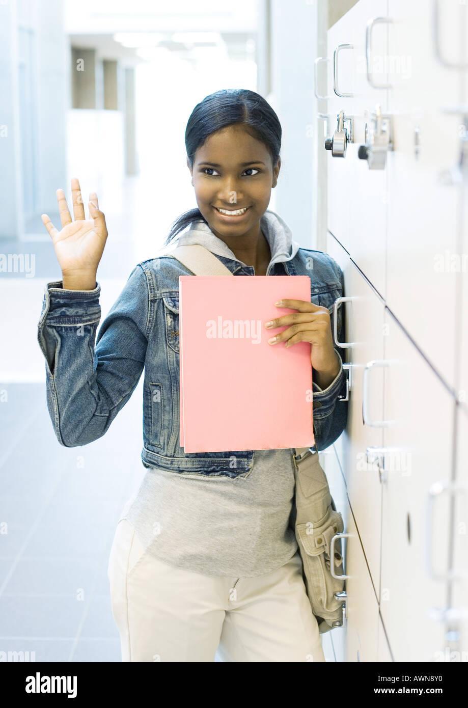 Teen girl standing by locker - Stock Image