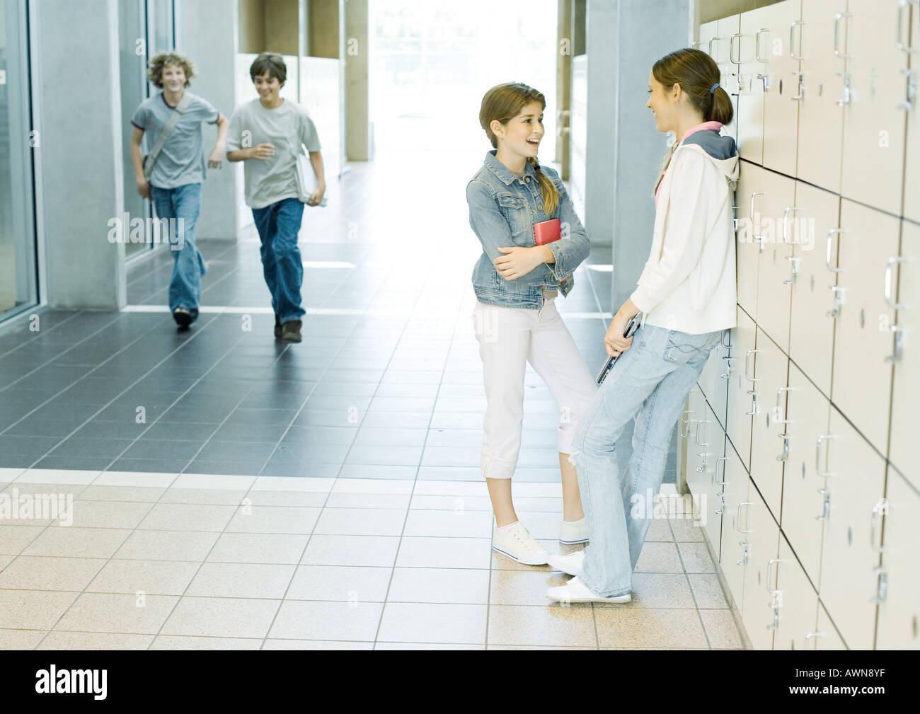 Two teen girls talking by lockers while boys run through hallway - Stock Image