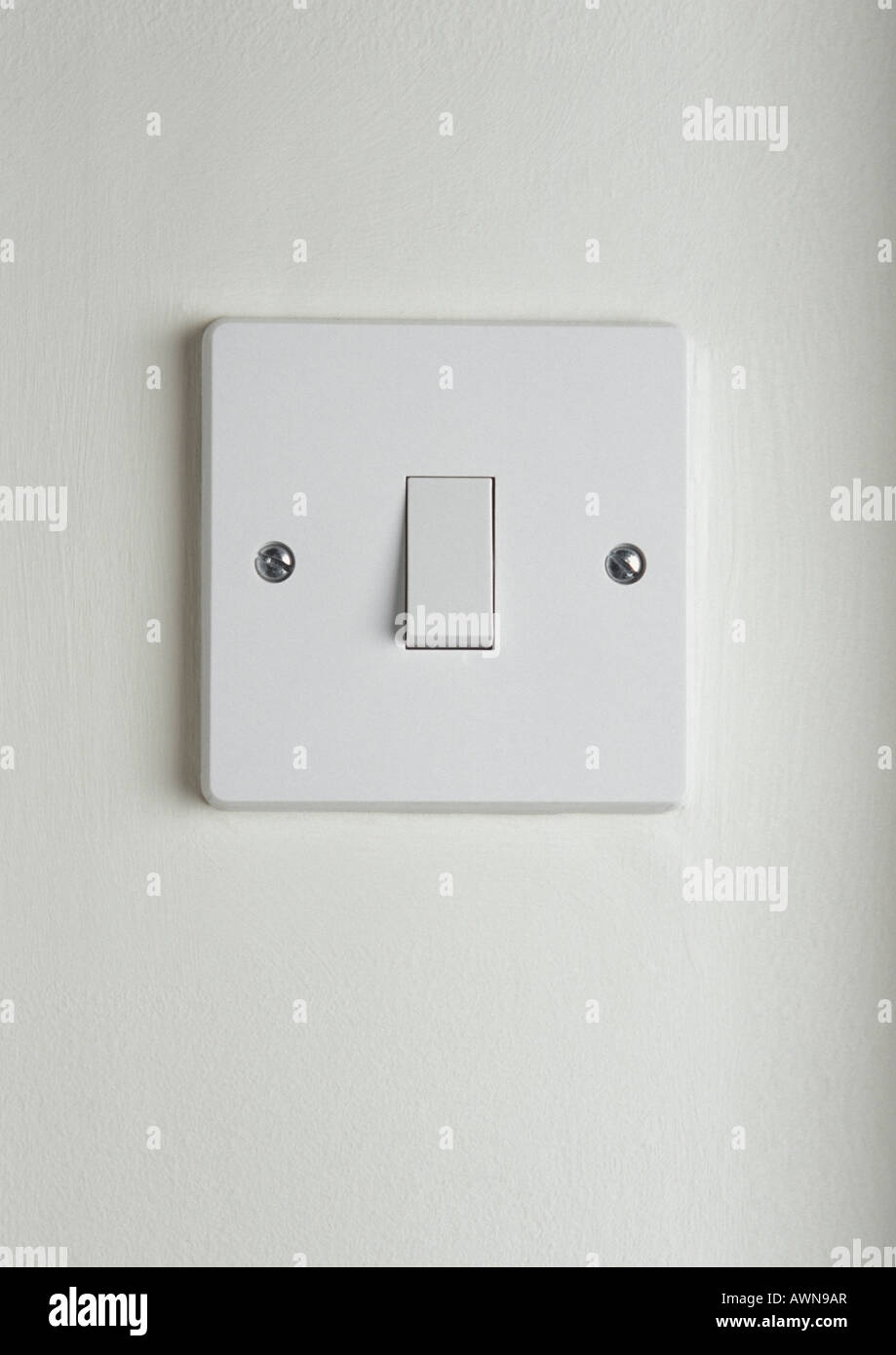 White plastic single light switch on white wall Stock Photo ...