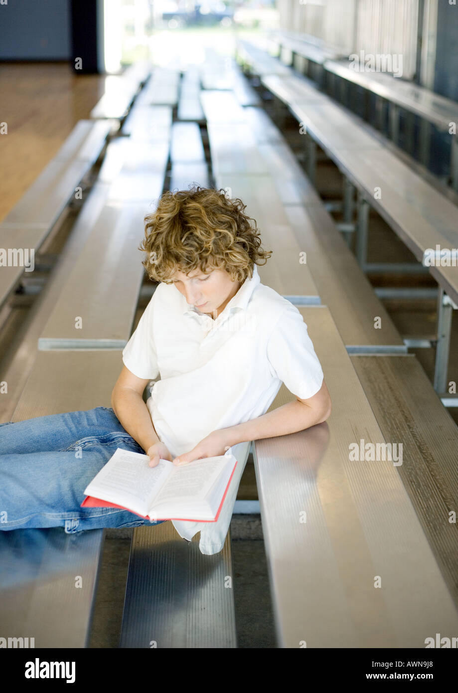 Teen boy reading book on bleachers - Stock Image