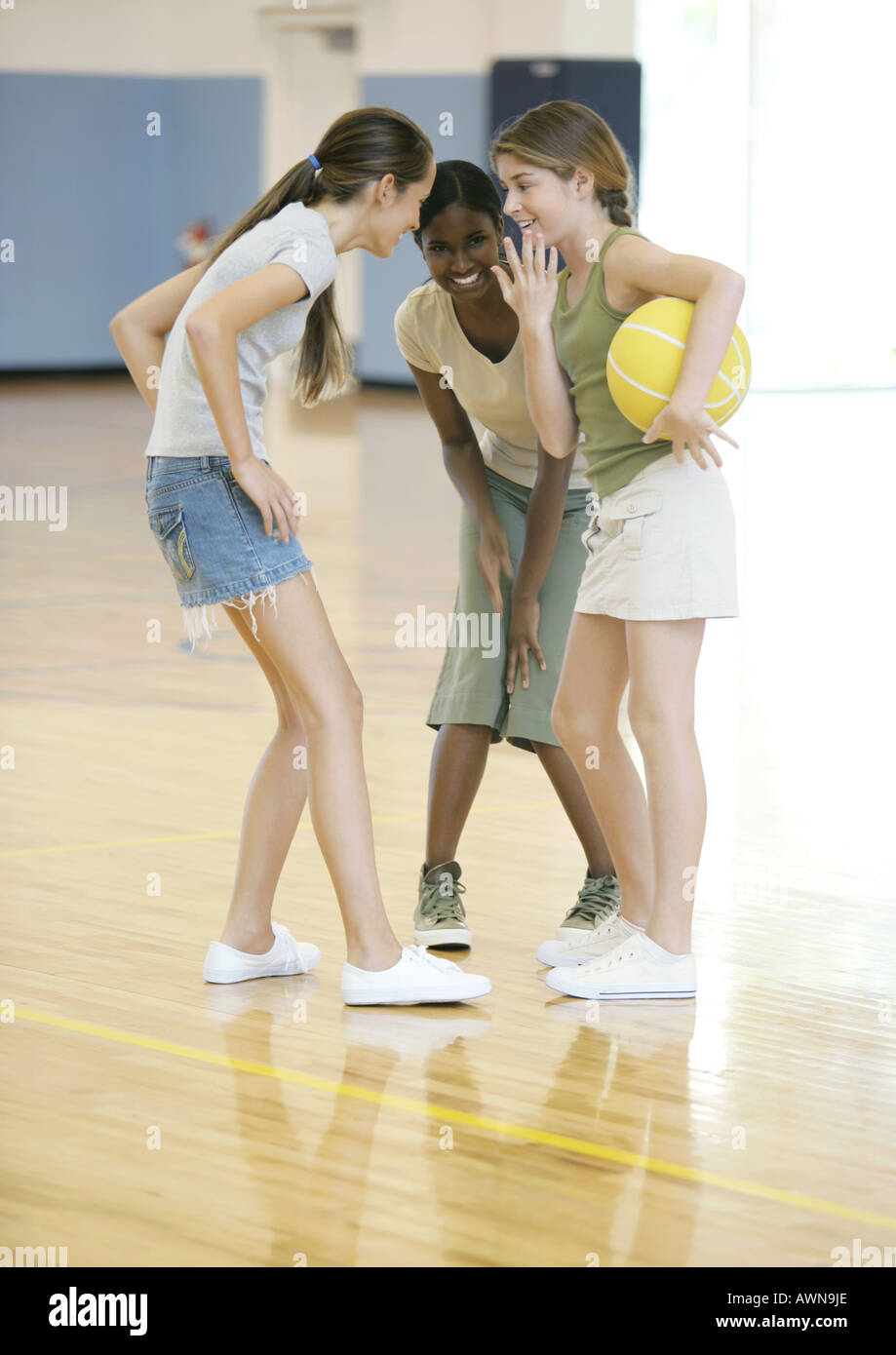 Three teen girls huddling in school gym - Stock Image