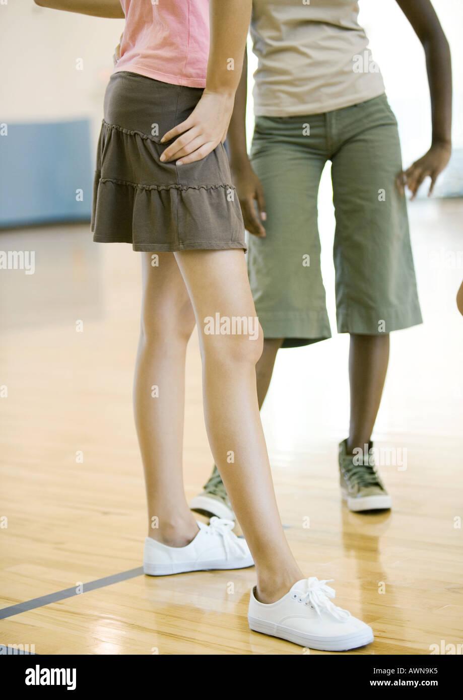 Teen girls standing in gym, waist down - Stock Image
