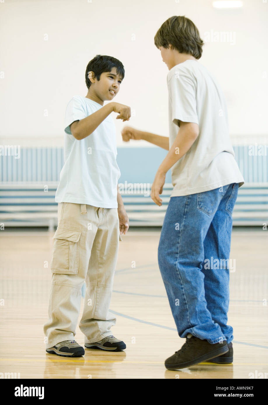 Two teen boys performing special handshake in school gym - Stock Image