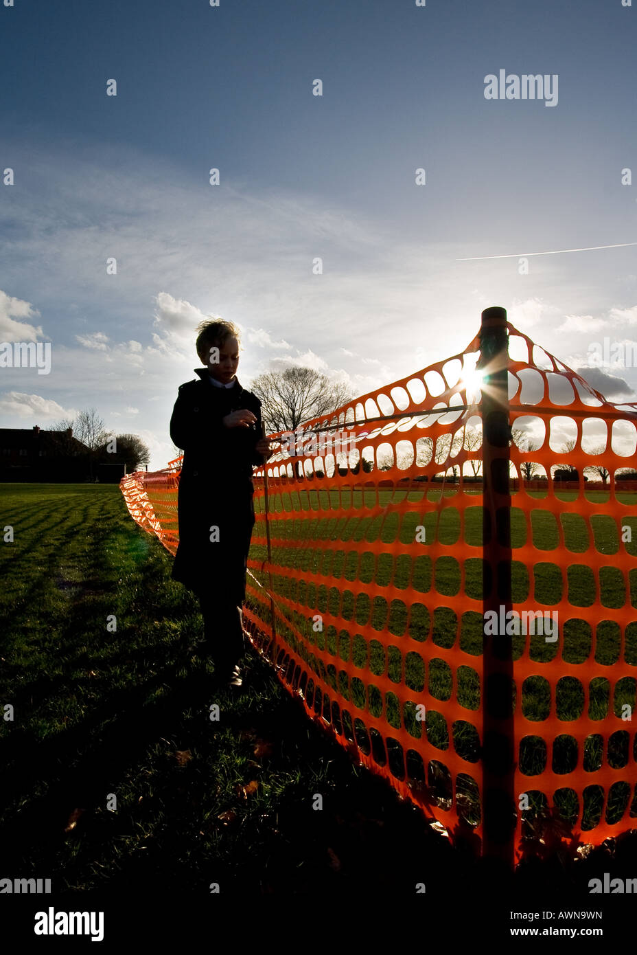 young boy on recreation ground with sun and silhouette - Stock Image