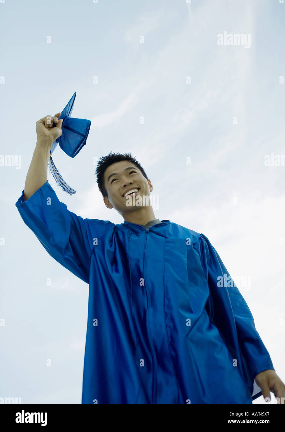 Male graduate taking off cap - Stock Image