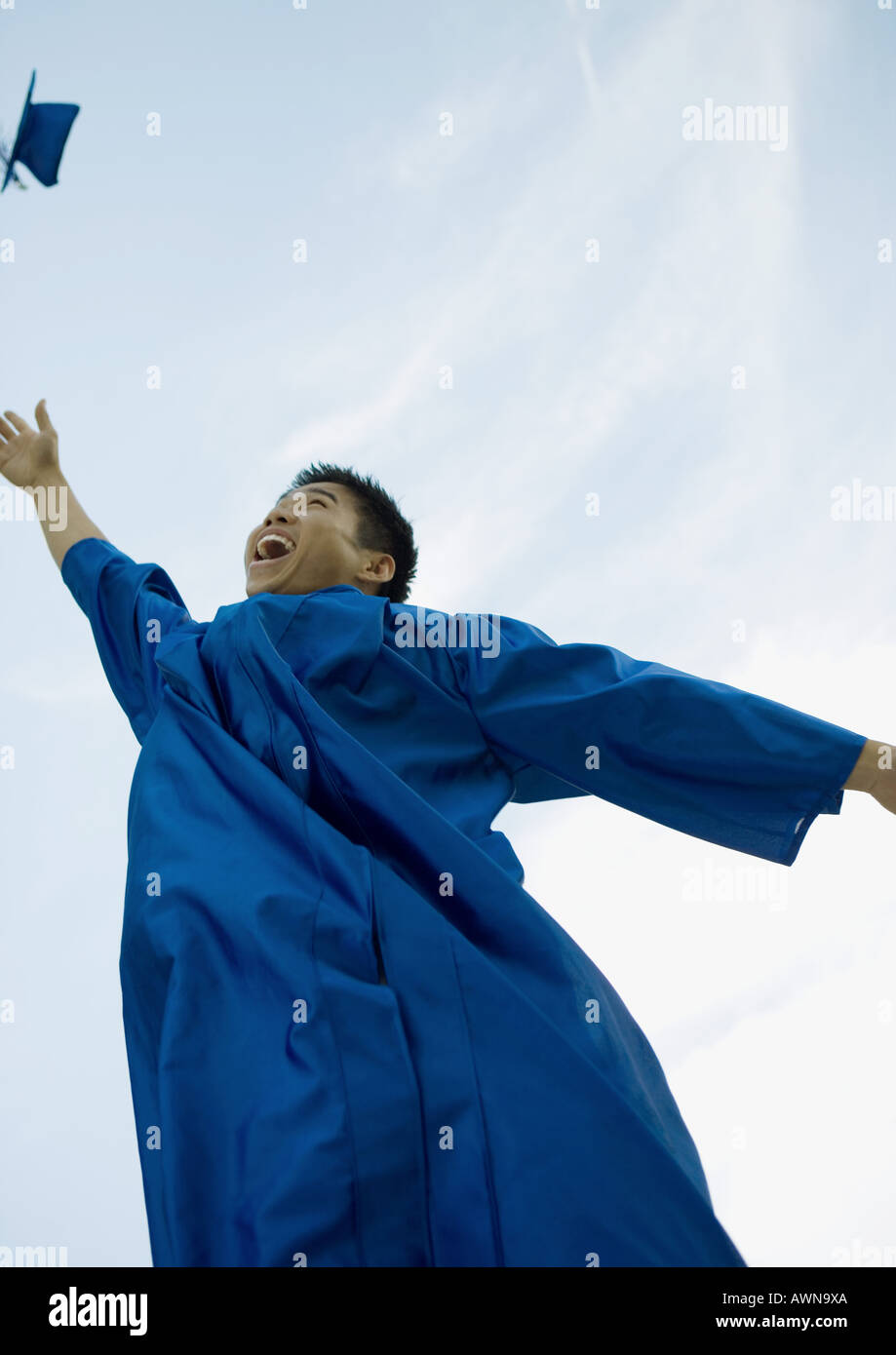 Male graduate throwing cap - Stock Image