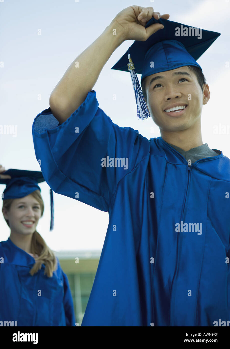 Graduates with hands on caps - Stock Image