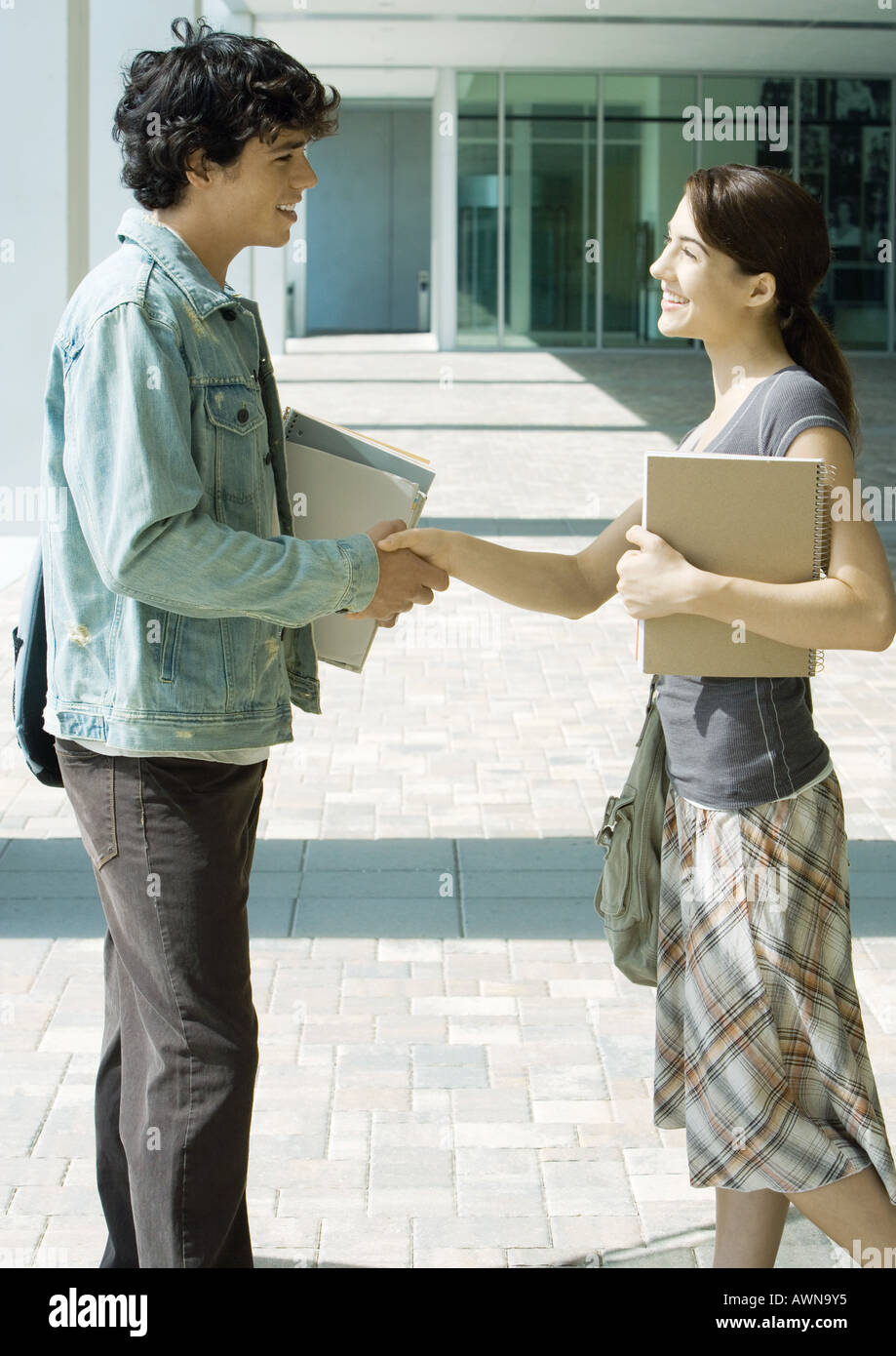 Students shaking hands on campus - Stock Image