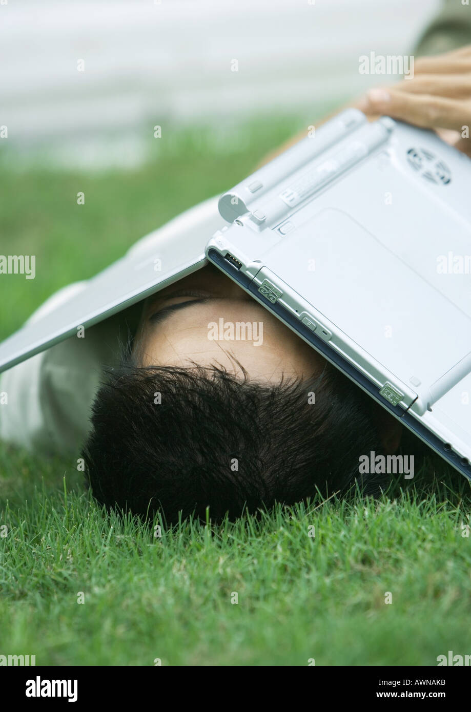 Man lying in grass with laptop covering face - Stock Image