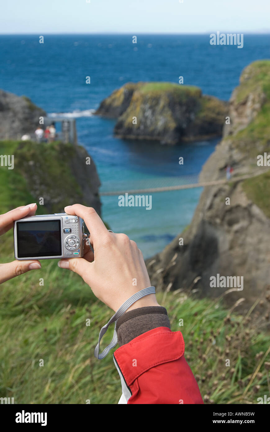 Woman photographing carrick-a-rede bridge Stock Photo