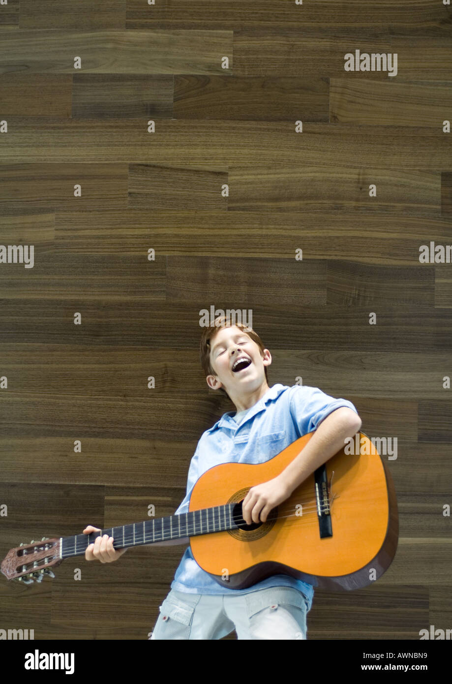 Boy playing guitar and singing - Stock Image