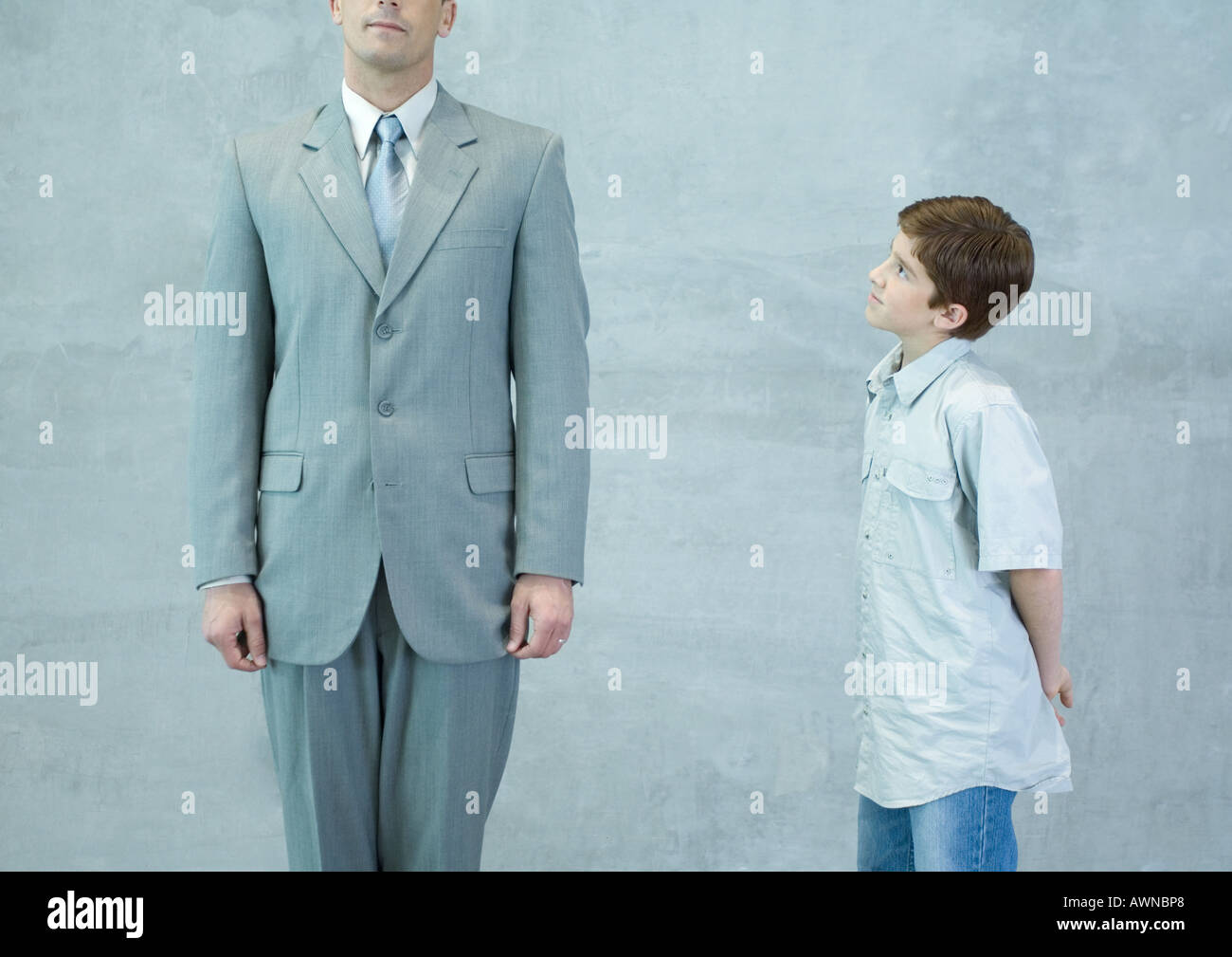Boy looking up at businessman - Stock Image