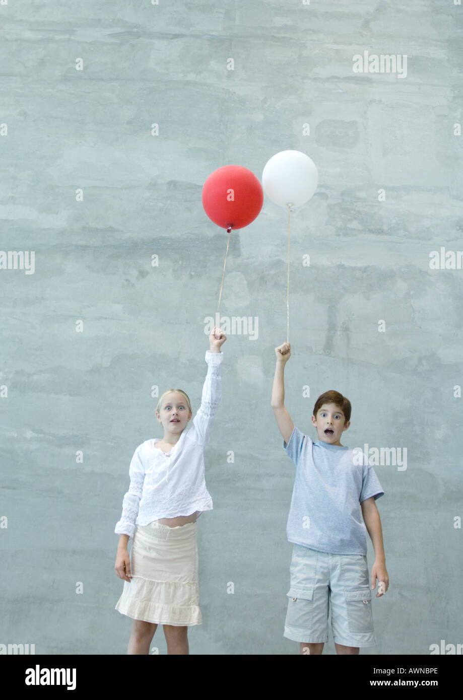 Two children holding balloons, making faces - Stock Image