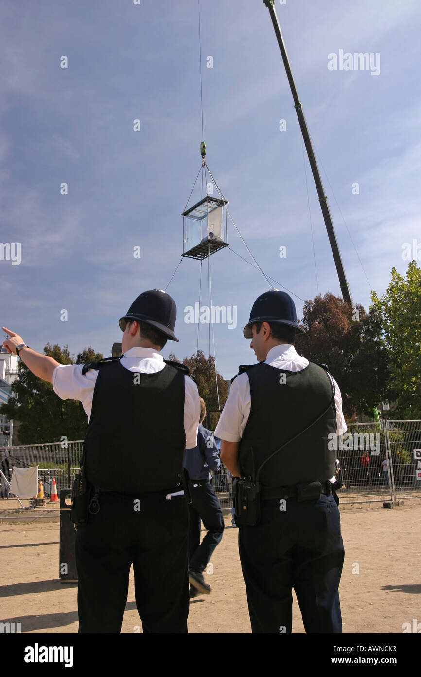 Two policeman one pointing directions standing under David Blane suspended in a plexiglass box by Tower Bridge London - Stock Image