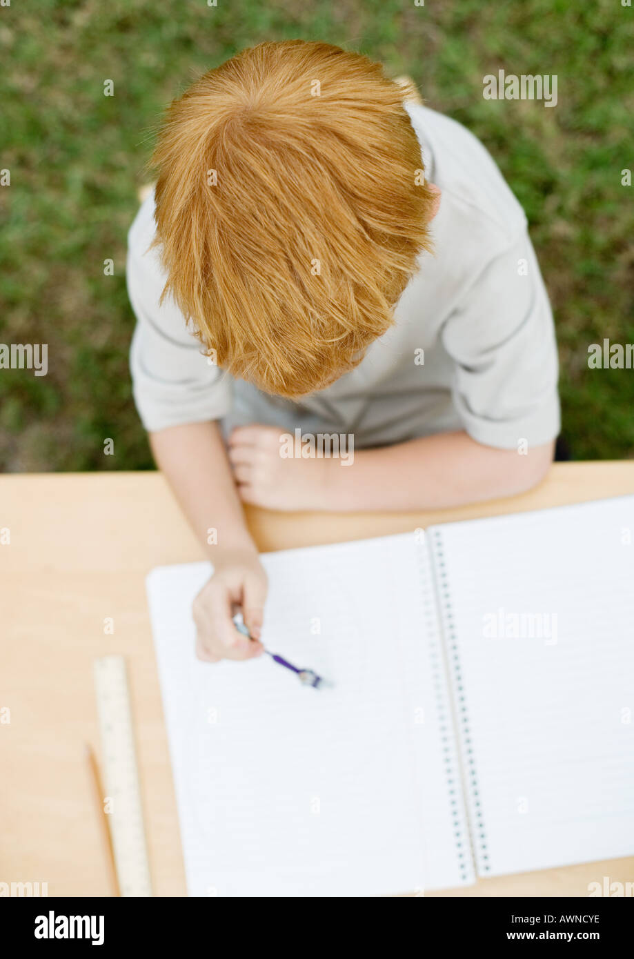 Boy sitting with open notebook Stock Photo