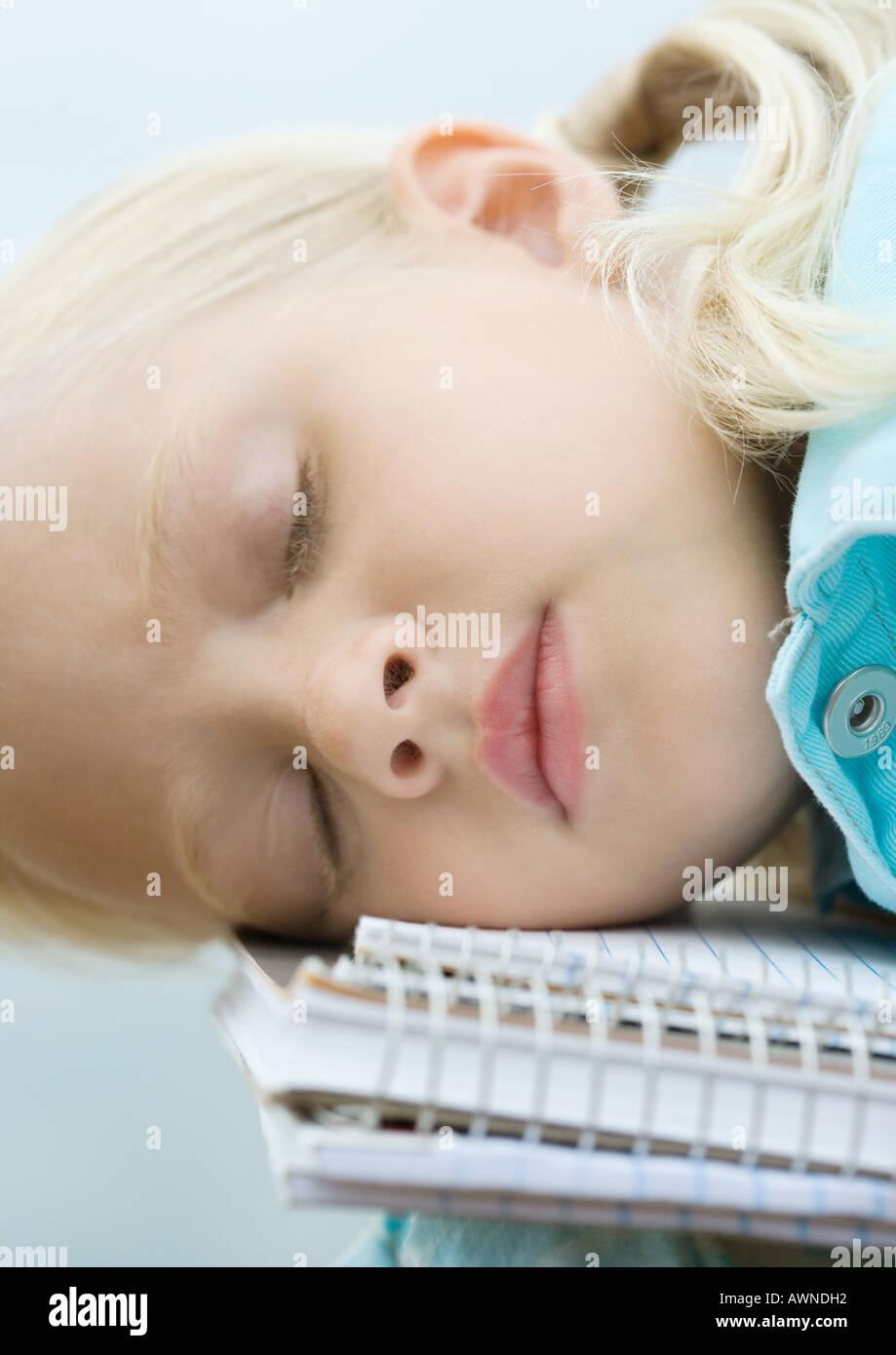 Girl sleeping on notebooks - Stock Image