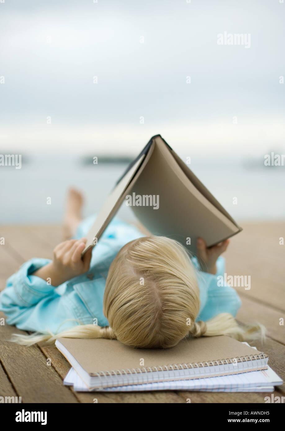 Girl reading book on dock - Stock Image
