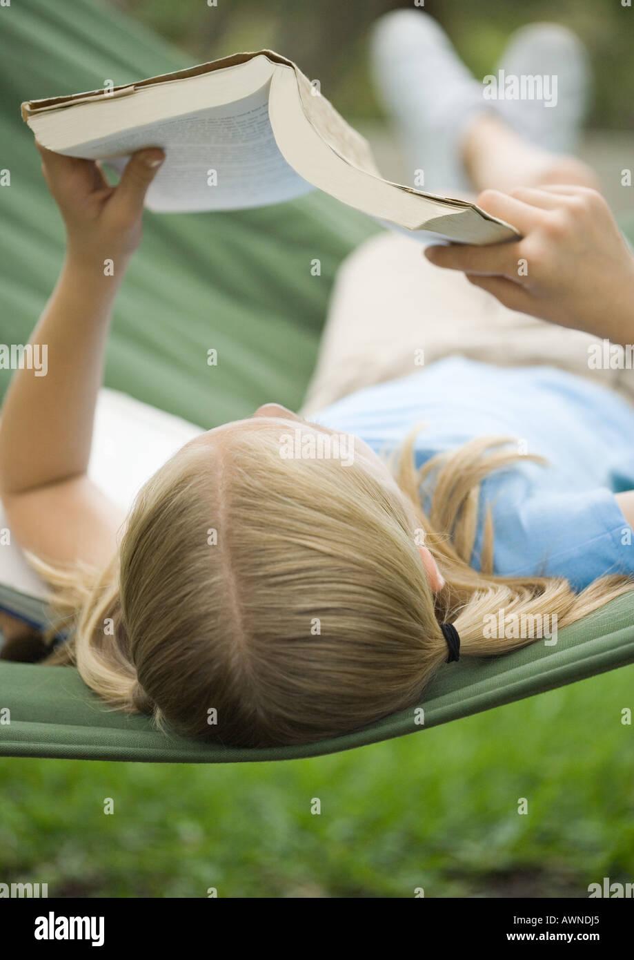 Girl reading book on hammock - Stock Image