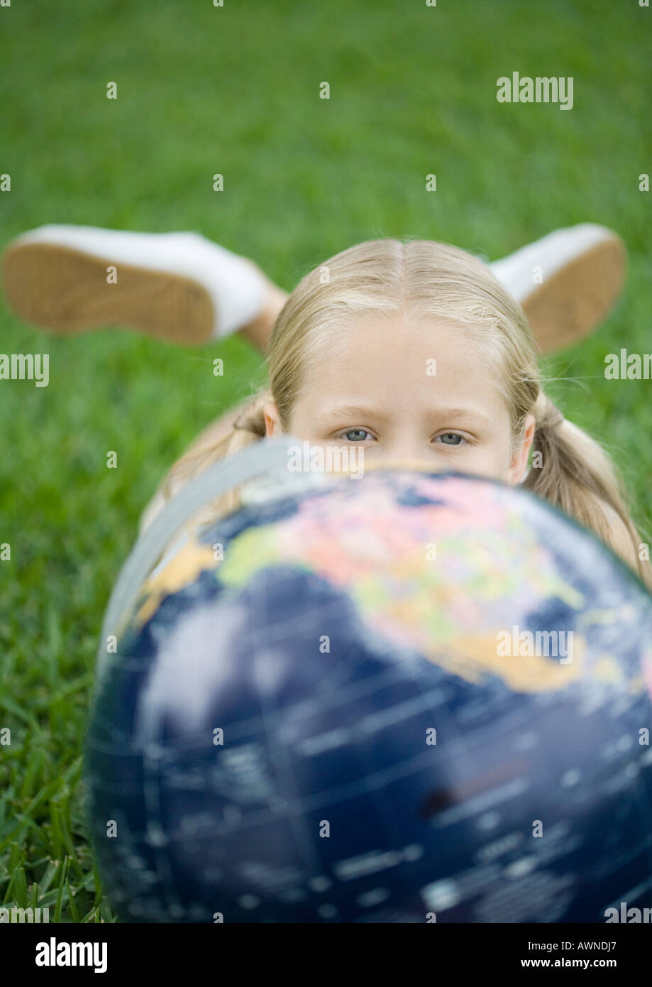 Girl lying on grass with globe, looking at camera - Stock Image