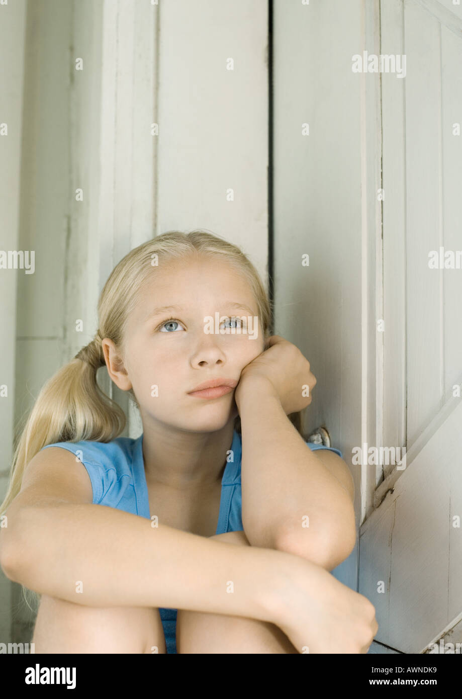Girl holding head, looking up - Stock Image