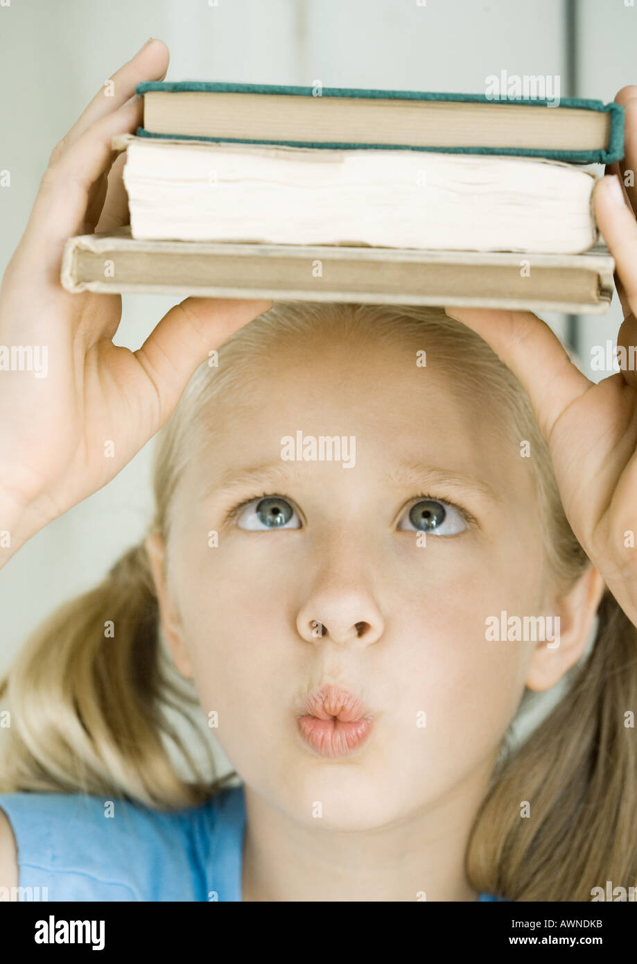 Girl holding stack of books on head, crossing eyes - Stock Image