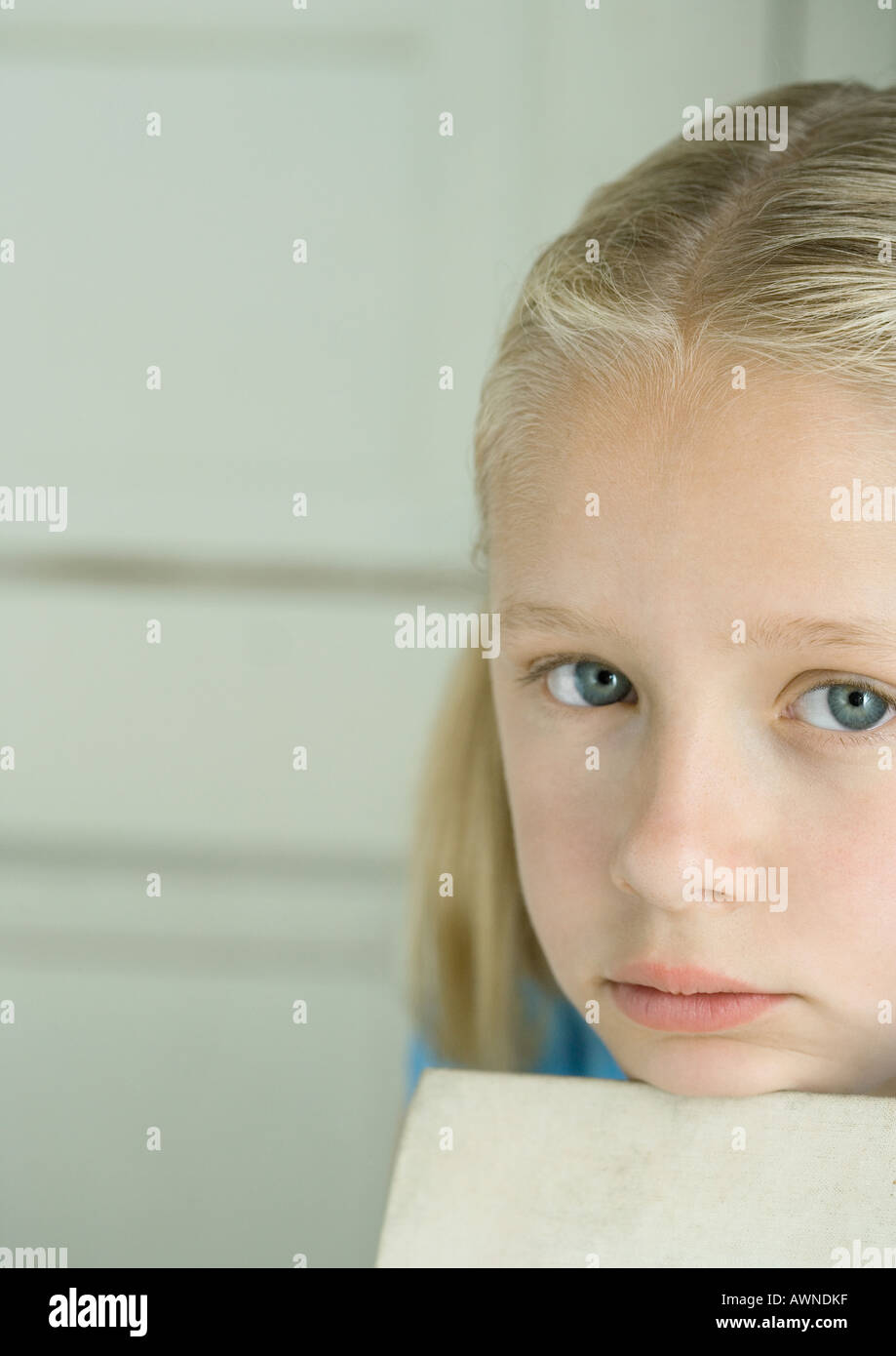 Girl resting head on edge of book, looking at camera - Stock Image